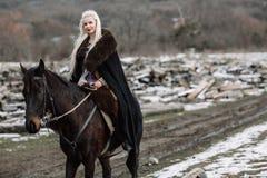 Beautiful blonde Viking in a black cape on horseback Royalty Free Stock Photos