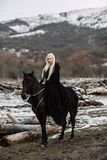 Beautiful blonde Viking in a black cape on horseback Royalty Free Stock Photography