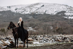 Beautiful blonde Viking in a black cape on horseback stock image