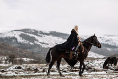 Beautiful blonde Viking in a black cape on horseback. Mountain snow in the background stock image
