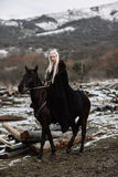 Beautiful blonde Viking in a black cape on horseback. Mountain snow in the background Stock Photo