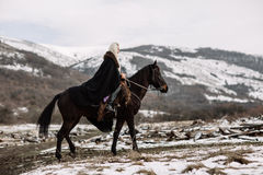 Beautiful blonde Viking in a black cape on horseback. Mountain snow in the background royalty free stock image