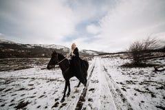 Beautiful blonde Viking in a black cape on horseback Royalty Free Stock Photo