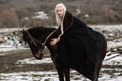 Beautiful blonde Viking in a black cape on horseback Stock Photos