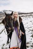 Beautiful blonde Viking in a black cape on horseback Stock Image