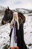 Beautiful blonde Viking in a black cape on horseback. Mountain snow in the background stock photography