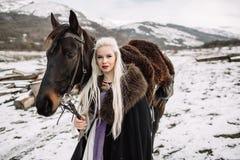 Beautiful blonde Viking in a black cape on horseback Royalty Free Stock Image
