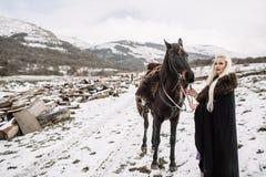 Beautiful blonde Viking in a black cape on horseback Stock Photo