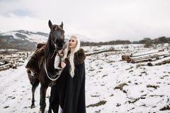 Beautiful blonde Viking in a black cape on horseback Stock Images
