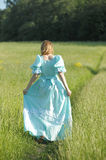 The beautiful blonde in a vintage dress goes, back to camera Royalty Free Stock Photo