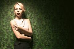 Beautiful blonde on vintage wall toned image Stock Photo