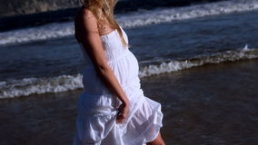 Beautiful blonde walking in white dress on sunny day at the beach stock footage