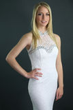 Beautiful blonde wearing a white dress. Over a gray background royalty free stock photo