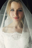 Beautiful blonde wedding bride in make-up and veil in a white dr Stock Image