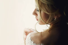 Beautiful blonde wedding bride in make-up and veil in a white dr Stock Photography