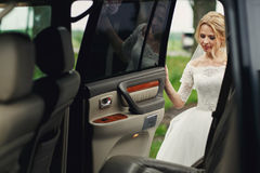 Beautiful blonde wedding bride in white dress getting into elega Royalty Free Stock Photo