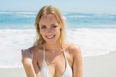 Beautiful blonde in white bikini smiling at camera on the beach Stock Photos