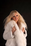 The beautiful blonde in a white fur coat Royalty Free Stock Images