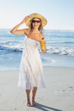 Beautiful blonde in white sundress on the beach with cocktail Stock Photos