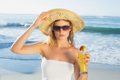 Beautiful blonde in white sundress on the beach with cocktail Stock Image