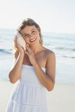 Beautiful blonde in white sundress on the beach listening to conch Royalty Free Stock Photography