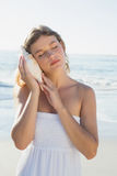 Beautiful blonde in white sundress on the beach listening to conch Stock Photo
