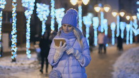 Beautiful blonde in winter clothes uses a tablet at night lights background stock video