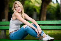 Beautiful blonde woamn rests on a bench in park Royalty Free Stock Images