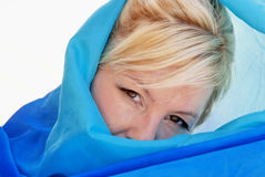 Beautiful blonde woman. With brown eyes with tilted head, half covered in blue silk cloth Stock Image