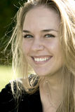 Beautiful blonde woman. With green eyes and smiling. Taken with backlighting Royalty Free Stock Photography