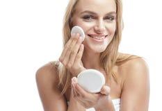 Beautiful blonde woman applying face powder Stock Image