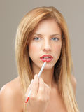 Beautiful blonde woman applying lip liner Royalty Free Stock Images