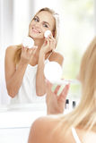 Beautiful blonde woman applying powder Royalty Free Stock Photos