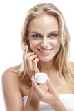 Beautiful blonde woman applying some facial cream on her cheek Stock Photography