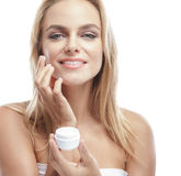 Beautiful blonde woman applying some facial cream on her cheek Royalty Free Stock Photos