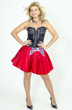 Beautiful blonde woman artist in chermnm corset with sequins and red skirt with belt bow. / Royalty Free Stock Image
