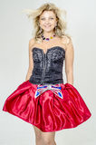 Beautiful blonde woman artist in chermnm corset with sequins and red skirt with belt bow. / Royalty Free Stock Photos