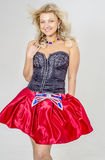Beautiful blonde woman artist in chermnm corset with sequins and red skirt with belt bow. / Royalty Free Stock Photography