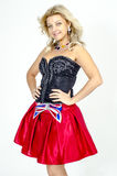 Beautiful blonde woman artist in chermnm corset with sequins and red skirt with belt bow. / Royalty Free Stock Photo