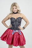 Beautiful blonde woman artist in chermnm corset with sequins and red skirt with belt bow. / Stock Images