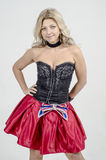 Beautiful blonde woman artist in chermnm corset with sequins and red skirt with belt bow. / Stock Photos