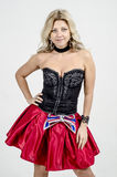 Beautiful blonde woman artist in chermnm corset with sequins and red skirt with belt bow. / Royalty Free Stock Images