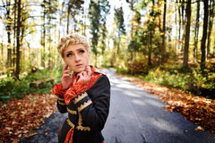 Beautiful blonde woman in autumn forest Royalty Free Stock Photography