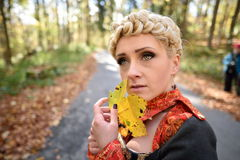 Beautiful blonde woman in autumn forest Stock Photo
