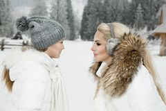 Beautiful blonde woman with baby, mom and daughter, on snow in winter clothes and in the background is a beautiful view o Stock Images