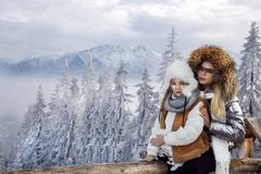 Beautiful blonde woman with baby, mom and daughter, on snow in winter clothes and in the background is a beautiful view o Royalty Free Stock Photos