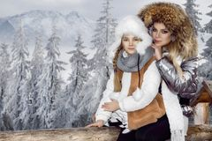 Beautiful blonde woman with baby, mom and daughter, on snow in winter clothes and in the background is a beautiful view o Stock Photography