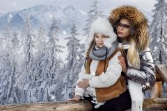 Beautiful blonde woman with baby, mom and daughter, on snow in winter clothes and in the background is a beautiful view o Stock Image