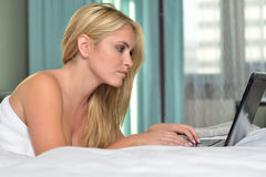 Beautiful blonde woman in bed -laptop computer Royalty Free Stock Photography