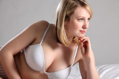 Beautiful blonde woman in bed with sexy cleavage Stock Photos